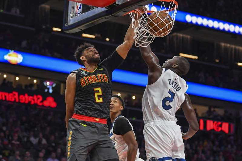 a man playing a game of basketball: Atlanta Hawks forward Jabari Parker (5) dunks against Minnesota Timberwolves center Gorgui Dieng (5) during the second half at State Farm Arena on November 25, 2019.