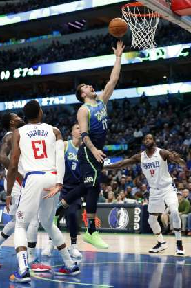 Dallas Mavericks forward Luka Doncic (77) shoots between Los Angeles Clippers' JaMychal Green (4) and Paul George (13) in the first half of an NBA basketball game in Dallas, Tuesday, Nov. 26, 2019. (AP Photo/Tony Gutierrez)