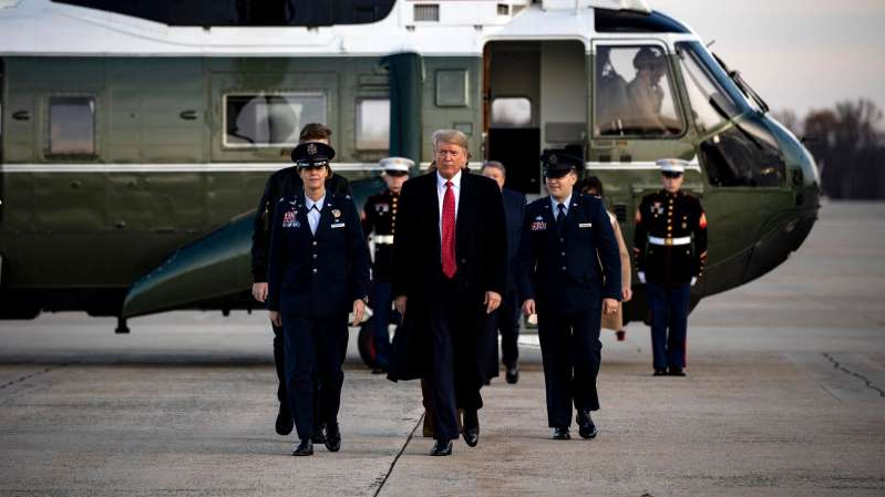 Donald Trump et al. standing next to a man in a suit and tie: President Trump at Joint Base Andrews in Maryland on Tuesday. The president said he planned to designate Mexican drug cartels as terrorist organizations.