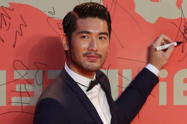 Godfrey Gao holding a sign posing for the camera