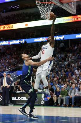Los Angeles Clippers forward Paul George (13) is fouled going up for a basket by Dallas Mavericks forward Dwight Powell in the second half of an NBA basketball game in Dallas, Tuesday, Nov. 26, 2019. (AP Photo/Tony Gutierrez)