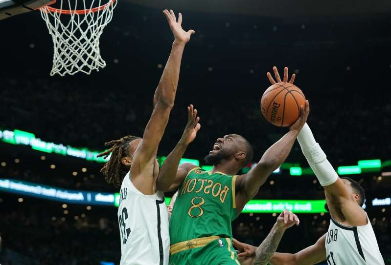 a person holding a basketball: Boston Celtics guard Kemba Walker (8) shoots against Brooklyn Nets forward Nicolas Claxton (33) in the second quarter at TD Garden on November 27, 2019.
