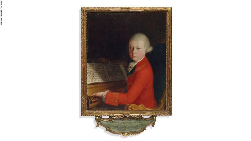 a person posing for a photo: The painting, which shows 13-year-old Mozart playing a harpsichord, smashed auction estimates when it went under the hammer in Paris on Wednesday.