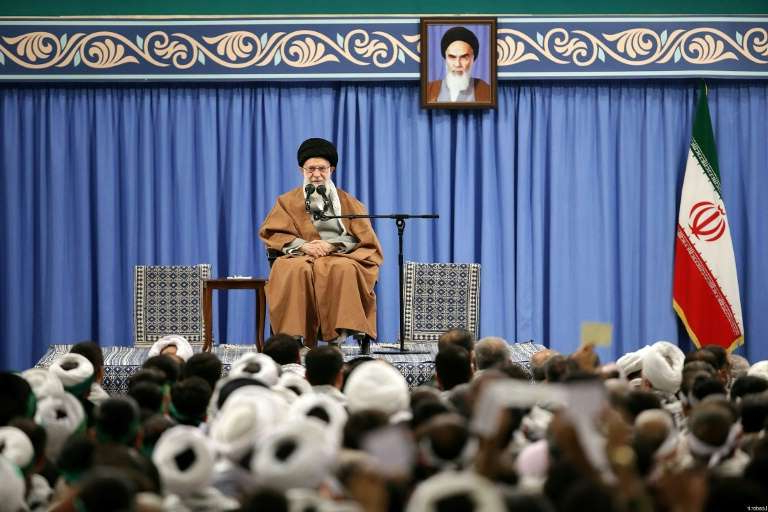 a person standing in front of a crowd: Iran's Supreme leader Ayatollah Ali Khamenei has said the country voiled 'a very dangerous plot' after the violent demonstrations