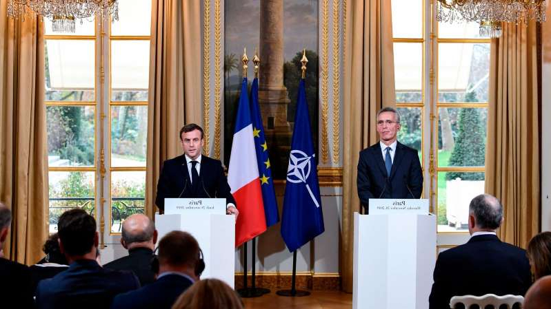 Emmanuel Macron et al. standing in front of a window: The NATO secretary general, Jens Stoltenberg, and President Emmanuel Macron of France speaking to reporters after a meeting on Thursday in Paris.