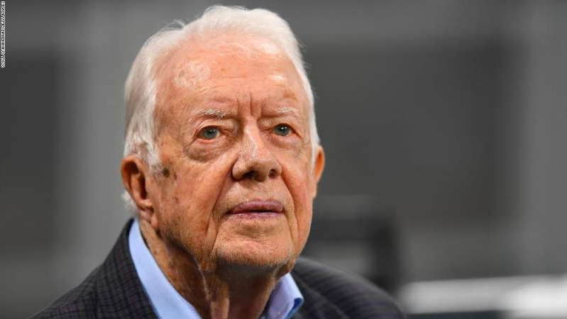 Jimmy Carter wearing a suit and tie: Former president Jimmy Carter prior to an NFL game on September 2018 in Atlanta.