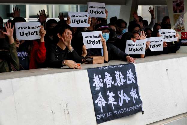 Slide 10 of 62: Office workers and pro-democracy protesters hold placards and raise their hands to represent their five demands as they stage a protests in Central district of Hong Kong, Wednesday, Nov. 27, 2019.