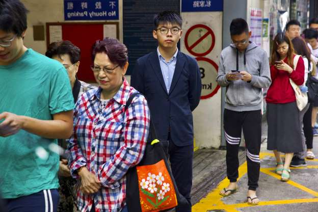 Slide 13 of 62: Pro-democracy activist Joshua Wong, center, stands in line to vote outside of a polling place, on Nov. 24.