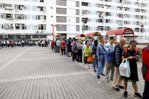 Slide 15 of 62: Voters queue outside a polling station during district council local elections on Nov. 24.