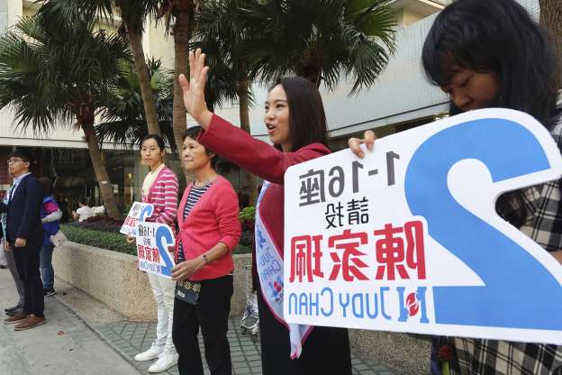 Slide 16 of 62: Pro-government candidate Judy Chan, second from left, campaigns ahead of local elections, on Nov. 23. Chanting