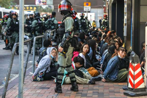 Slide 17 of 62: People are detained by police near the Hong Kong Polytechnic University in Hung Hom district of Hong Kong on November 18, 2019. - Pro-democracy demonstrators holed up in a Hong Kong university campus set the main entrance ablaze November 18 to prevent surrounding police moving in, after officers warned they may use live rounds if confronted by deadly weapons.