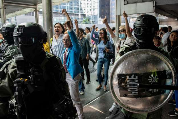 Slide 18 of 62: Riot police stand in between pro-China supporters (C) as they shout slogans and gesture towards office workers (not pictured) gathering in support of pro-democracy protesters during a lunch break rally in the Central district of Hong Kong on November 22, 2019. - China on November 21 accused the United States of seeking to