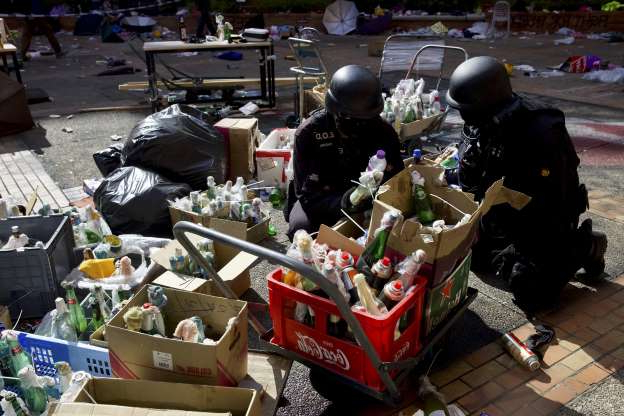 Slide 2 of 62: Police from Explosive Ordnance Disposal (EOD) unit check on the molotov cocktails left over by protesters at the compound of the Hong Kong Polytechnic University campus in Hong Kong, Thursday, Nov. 28, 2019. Police safety teams Thursday began clearing the university that was a flashpoint for clashes with protesters, and an officer said any holdouts still hiding inside would not be immediately arrested.