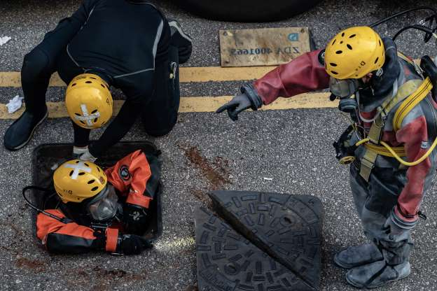 Slide 27 of 62: HONG KONG, CHINA - NOVEMBER 20:  Fire Services Department rescue diver prepares to enter the sewage system to search for protesters who escape from The Hong Kong Polytechnic University on November 20, 2019 in Hong Kong, China. Anti-government protesters armed with bricks, firebombs, and bows and arrows fought with the police at university campuses over the past week as demonstrations in Hong Kong stretched into its sixth month with demands for an independent inquiry into police brutality, the retraction of the word