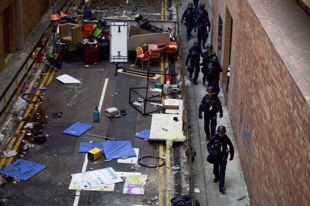 Slide 3 of 62: Policemen from Explosive Ordnance Disposal (EOD) unit walk by the debris scattered on a road as they enter the Hong Kong Polytechnic University campus to search for dangerous materials in Hong Kong, Thursday, Nov. 28, 2019. Police safety teams Thursday began clearing the university that was a flashpoint for clashes with protesters, and an officer said any holdouts still hiding inside would not be immediately arrested.