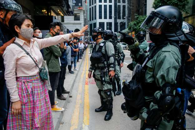 Slide 30 of 62: A protestor (R) reacts to police officers during an anti-government protest in Hong Kong, China, 19 November 2019. Hong Kong is in its sixth month of mass protests, which were originally triggered by a now withdrawn extradition bill, and have since turned into a wider pro-democracy movement