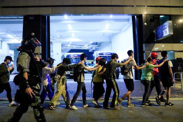 Slide 40 of 62: Protesters are escorted by police out of the campus of Hong Kong Polytechnic University (PolyU) during clashes with police in Hong Kong, China November 18, 2019. REUTERS/Thomas Peter