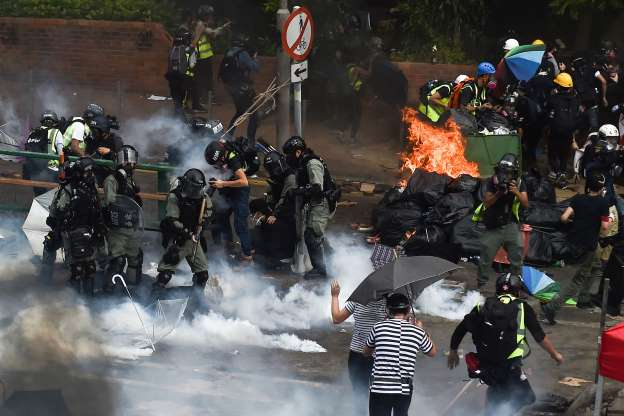 Slide 42 of 62: Riot police (R) make arrests as protesters (L) attempt to find safe passage out of the Hong Kong Polytechnic University campus in Hung Hom district of Hong Kong on November 18, 2019. - Pro-democracy demonstrators holed up in a Hong Kong university campus set the main entrance ablaze on November 18 after police warned they may use live rounds, deepening fears over how nearly six months of unrest across the city will end. (Photo by Ye Aung Thu / AFP) (Photo by YE AUNG THU/AFP via Getty Images)