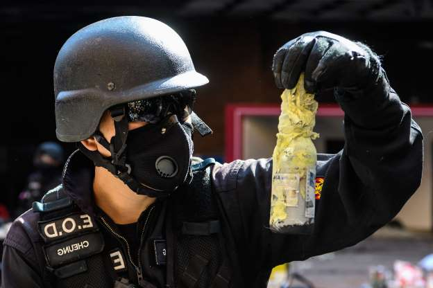 Slide 6 of 62: A Hong Kong Police Explosive Ordnance Disposal Bureau (EOD) personnel handles a Molotov cocktail as his team searches for explosives and chemicals at the Hong Kong Polytechnic University in the Hung Hom district of Hong Kong on November 28, 2019, over a week after police surrounded the building while pro-democracy protesters were still barricaded inside.