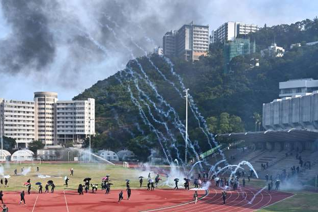 Slide 60 of 62: Protesters react after police fired tear gas at the Chinese University of Hong Kong (CUHK), in Hong Kong on November 12, 2019. - Hong Kong protesters struck the city's transport network for a second day running on November 12 as western powers voiced concern over spiralling violence after police shot a young demonstrator and another man was set on fire. (Photo by Philip FONG / AFP) (Photo by PHILIP FONG/AFP via Getty Images)
