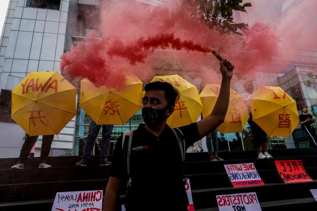 Slide 9 of 62: Activists holding umbrellas in support of pro-democracy protesters in Hong Kong stand in front of the Chinese consulate in the financial district of Manila on November 27, 2019.