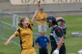 a group of baseball players playing a football game: There were few people watching in the stands at North Sydney Oval in 2009 when a young Ellyse Perry was in action at the ICC Women's World Cup.
