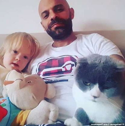 a man holding a baby next to a cat: Luca Trapanese, 41, from Italy, has gained thousands of followers across social media from documenting his life with his adopted daughter Alba (pictured together at home with their cat Giorgio)
