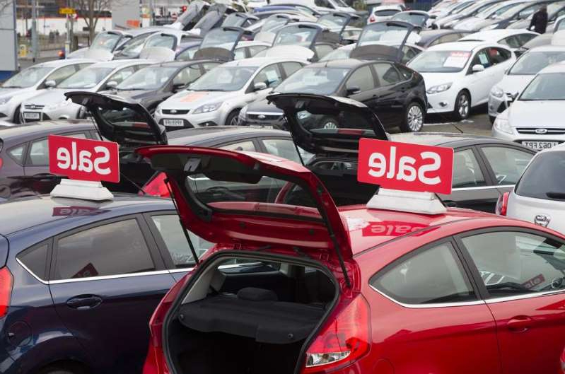 a red car parked in a parking lot: Influx of second-hand petrol cars hammers used values