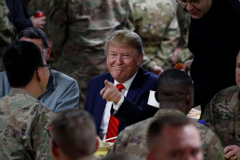 Donald Trump et al. looking at each other: FILE PHOTO: U.S. President Donald Trump makes an unannounced visit to U.S. troops at Bagram Air Base in Afghanistan