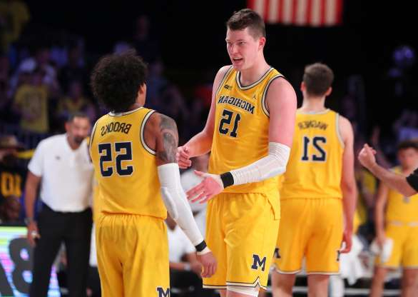 Slide 1 of 13: Michigan center Jon Teske and guard Eli Brooks celebrate during the first half against Gonzaga on Friday, Nov. 29, 2019, in Paradise Island, Bahamas.