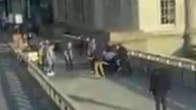 a blurry photo of a building: Members of the public grapple with knife suspect