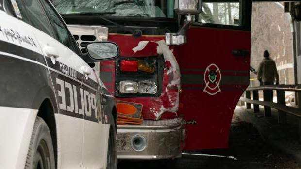 a car parked in front of a bus: Winnipeg police block the fire truck that was allegedly stolen on Friday.