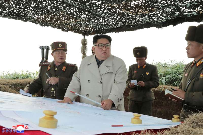 a group of people standing around a table: North Korean leader Kim Jong Un visits the Changrindo defensive position on the west front