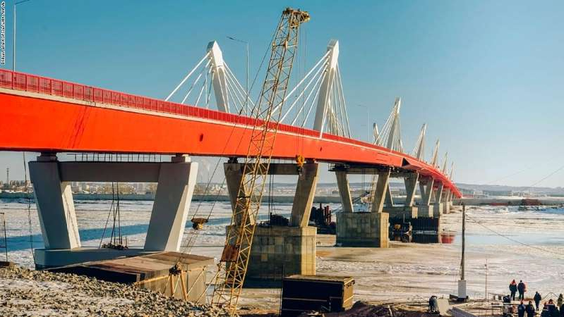 a large ship in a body of water: 6089559 29.11.2019 A general view shows the new cross-border automobile cable-stayed bridge across the Amur River connecting the Russian city of Blagoveshchensk and the Chinese city of Heihe, outside the Far Eastern city of Blagoveshchensk, Russia. The bridge is the only road bridge across the Amur on the Russian-Chinese border and is expected to come into service by April 2020. The construction of the bridge began in 2016 and last May the two sections of the bridge were connected. Dmitry Tupikov/Sputnik via AP
