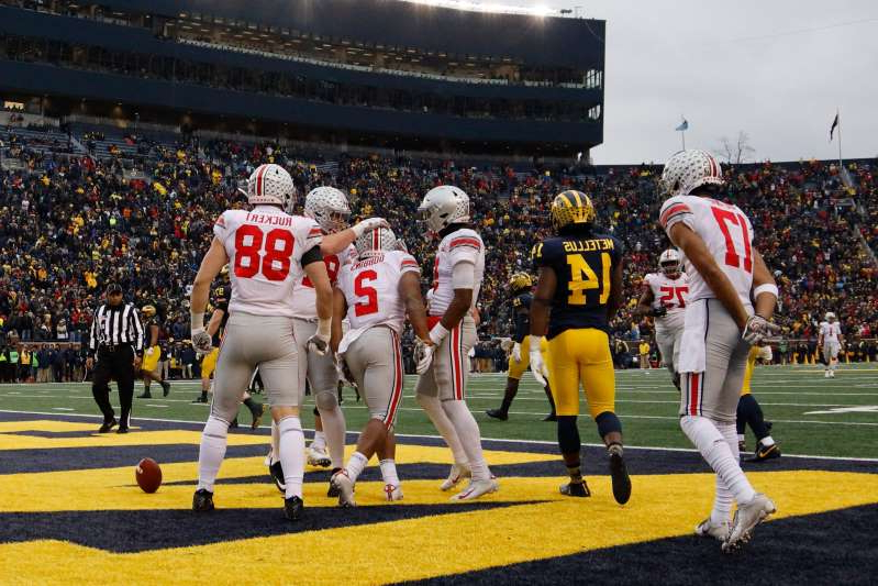 a group of baseball players playing a football game: Ohio State running back J.K. Dobbins (2) is congratulated by teammates after he rushes for a touchdown in the second half against Michigan.