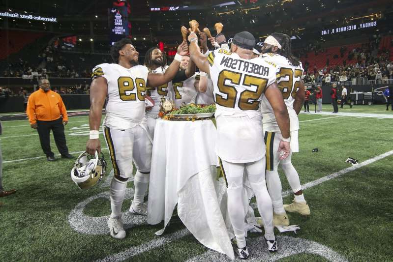 a group of people posing for the camera: New Orleans Saints linebacker Craig Robertson (52) and defensive tackle Shy Tuttle (99) celebrate after a game with turkey legs against the Atlanta Falcons on Thanksgiving Day at Mercedes-Benz Stadium on November 28, 2019.