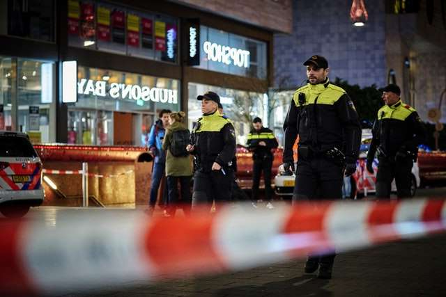 a group of people standing in front of a building: The incident occurred in a busy shopping area, which was packed with people on Black Friday (Phil Nijhuis/AP)