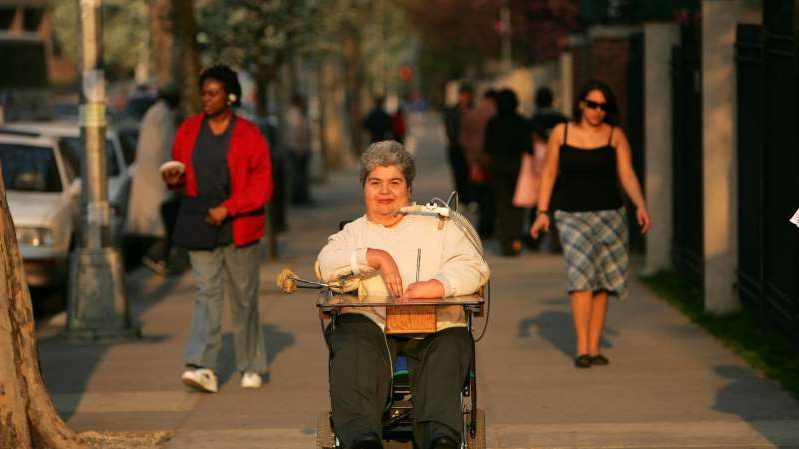 a group of people walking down the street: Marilyn Saviola in 2005. She joined the battle for the rights of people with disabilities in the late 1960s, when it was still relatively new.