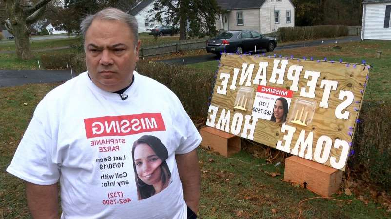 a man holding a sign posing for the camera: Edward Parze stands next to a large sign Monday, November 18, 2019, outside his Freehold home that asks his missing daughter Stephanie to come home. The woman has been missing since the night before Halloween.