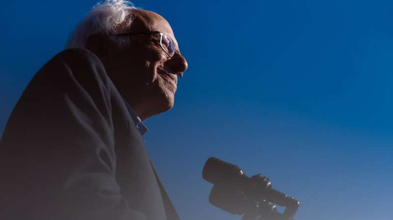 a man standing in front of a blue sky: Senator Bernie Sanders at an October campaign rally in Queens.