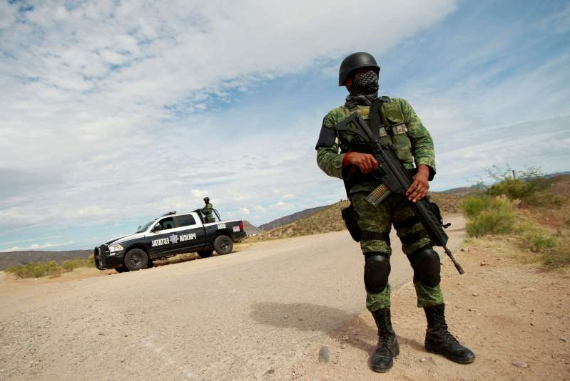 a man wearing a military uniform: FILE PHOTO: A soldier assigned to the National Guard is pictured at a checkpoint as part of an ongoing security operation by the federal government near the Mexican-American Mormon community of La Mora