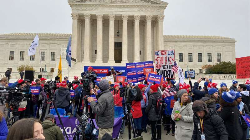 a group of people standing in front of a crowd: Supporters of gun-control legislation rallying in front of the Supreme Court on Monday.