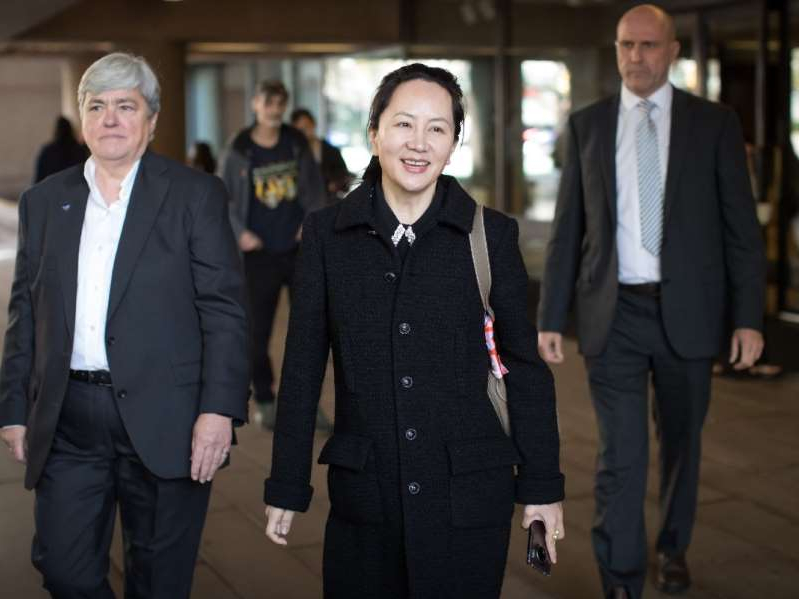 a group of people standing next to a man in a suit and tie: Huawei chief financial officer Meng Wanzhou, centre, who is out on bail and remains under partial house arrest after she was detained last year at the behest of American authorities, is escorted by members of a private security team as she leaves B.C. Supreme Court during a lunch break from a hearing, in Vancouver, on Tuesday, September 24, 2019.