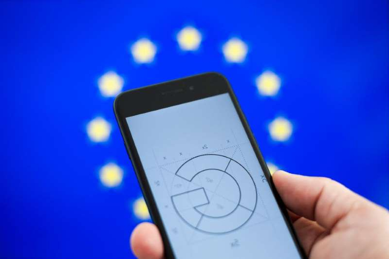 a hand holding a cell phone screen with text: Google has run afoul of EU competition rules before. Jaap Arriens/NurPhoto via Getty Images