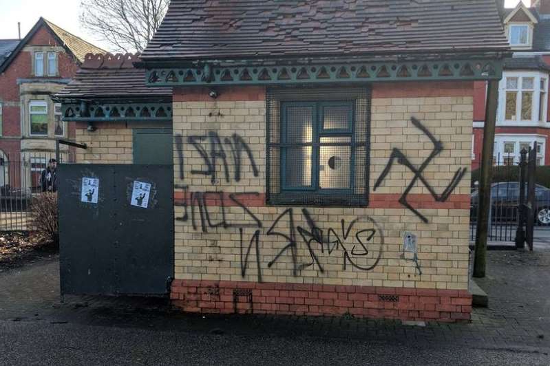 a large brick building with graffiti on the side of a house: The building in Grange Gardens