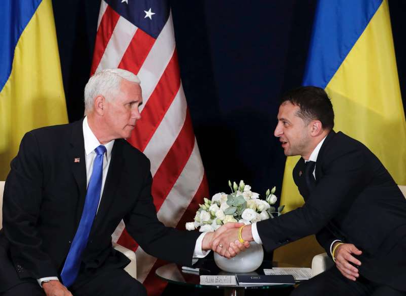 a man and woman cutting a wedding cake: Ukraine's President Volodymyr Zelensky, left, shakes hands with U.S. Vice President Mike Pence, in Warsaw, Poland on Sept. 1, 2019.  A Washinton Post article published on Oct. 2, 2019 reported President Donald Trump used Pence in his attempt to pressure the new Ukrainian president to dig up dirt on Joe Biden, but is not conclusive on how much Pence knew about Trump's efforts.