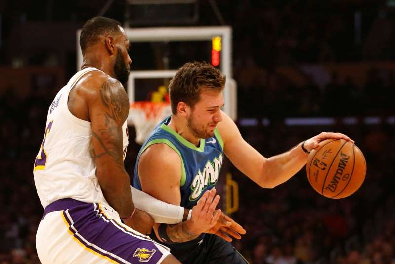 a man holding a basketball: In the Mavericks' 114-100 win over the Lakers and LeBron James (right) on Sunday in Los Angeles, Luka Doncic scored 27 points, dished out 10 assists and grabbed nine boards.