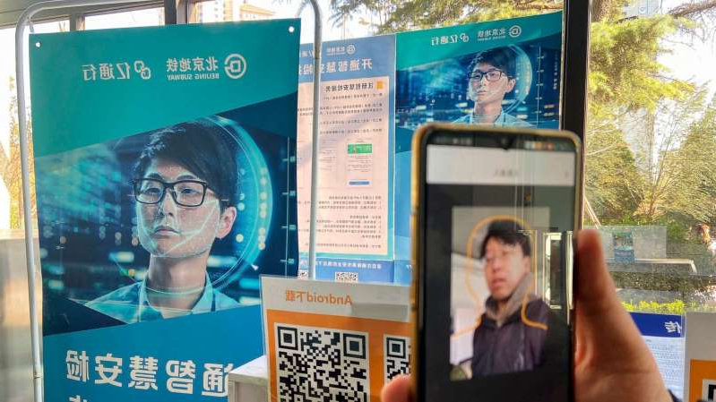 a person holding a sign: A person shows the facial recognition shown through the app at the Fuchengmen subway station in Beijing, China, Nov. 28, 2019.