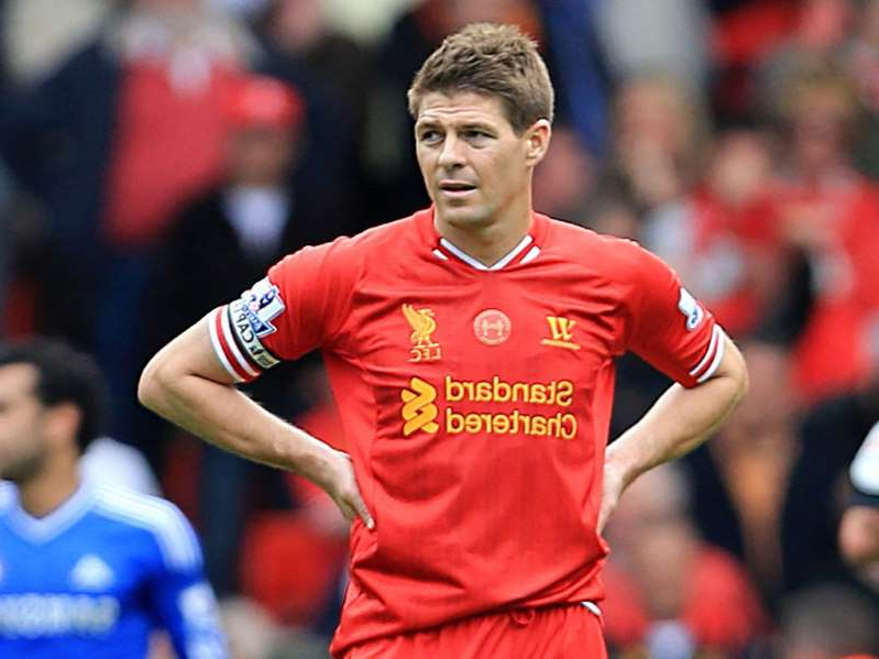 Alex Curran holding a football ball: Steven Gerrard looks dejected after that slip against Chelsea