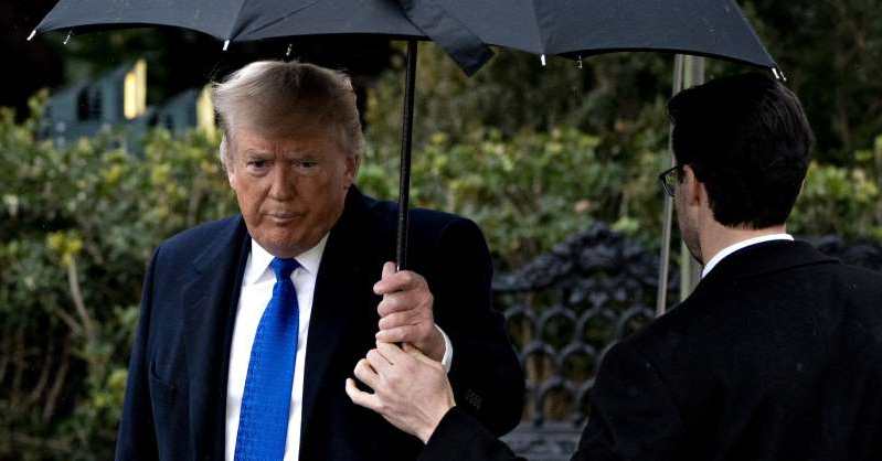 Donald Trump wearing a suit and tie holding his umbrella: U.S. President Donald Trump arrives to speak to members of the media before boarding Marine One on the South Lawn of the White House in Washington, D.C., U.S., on Monday, Dec. 2, 2019.